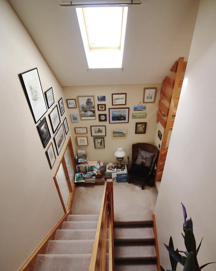 Staircase with Orcadian art and books.